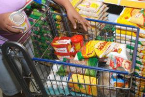 um carrinho de supermercado cheio de produtos básicos.